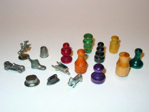 Monopoly wood and metal player tokens.
